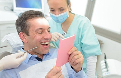 Man in dental chair looking at his smile
