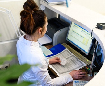 A young female sitting behind a computer at the front desk of a dentist's office