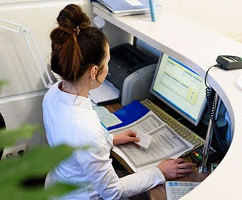 receptionist at a dental office typing in patients insurance information into a computer