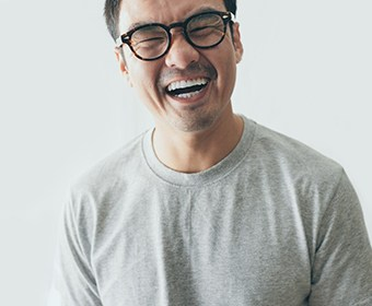 person with glasses who is laughing