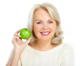 older woman smiling holding green apple