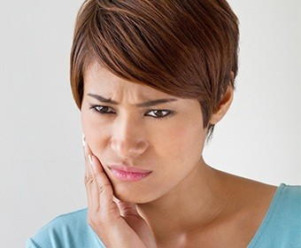 Woman in pain holding her cheek