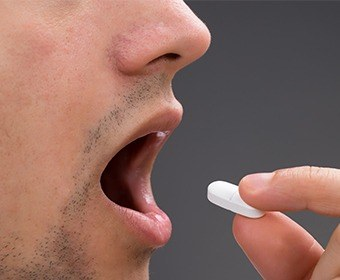 Man taking an oral sedative pill