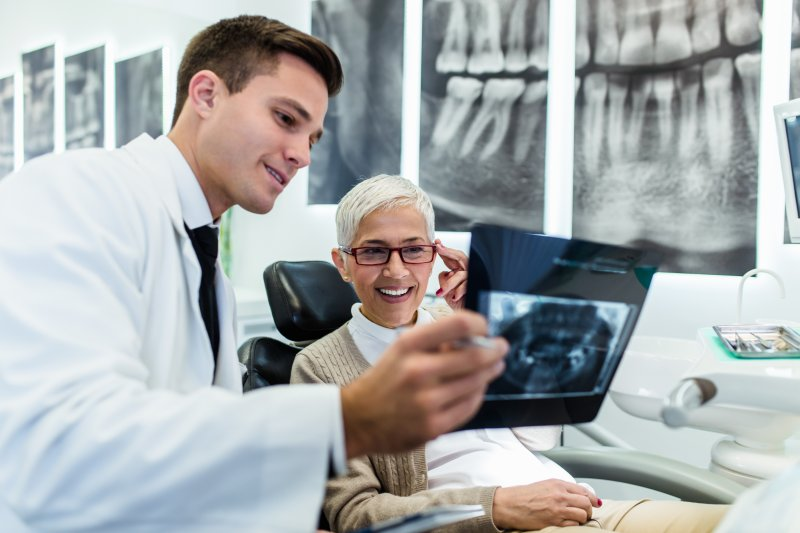an older woman reviewing an X-ray with her dentist