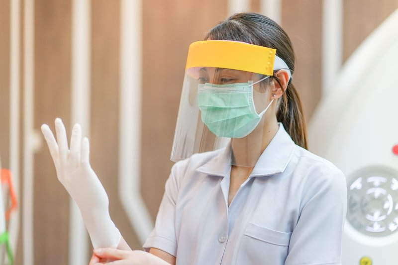 a dental staff member putting on gloves while donning a face mask and shield